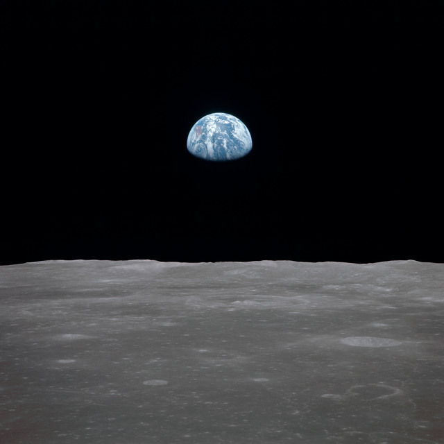 AS11-44-6560 - Apollo 11 - Apollo 11 Mission image - View of moon limb, with Earth on the horizon, Mare Smythii Region