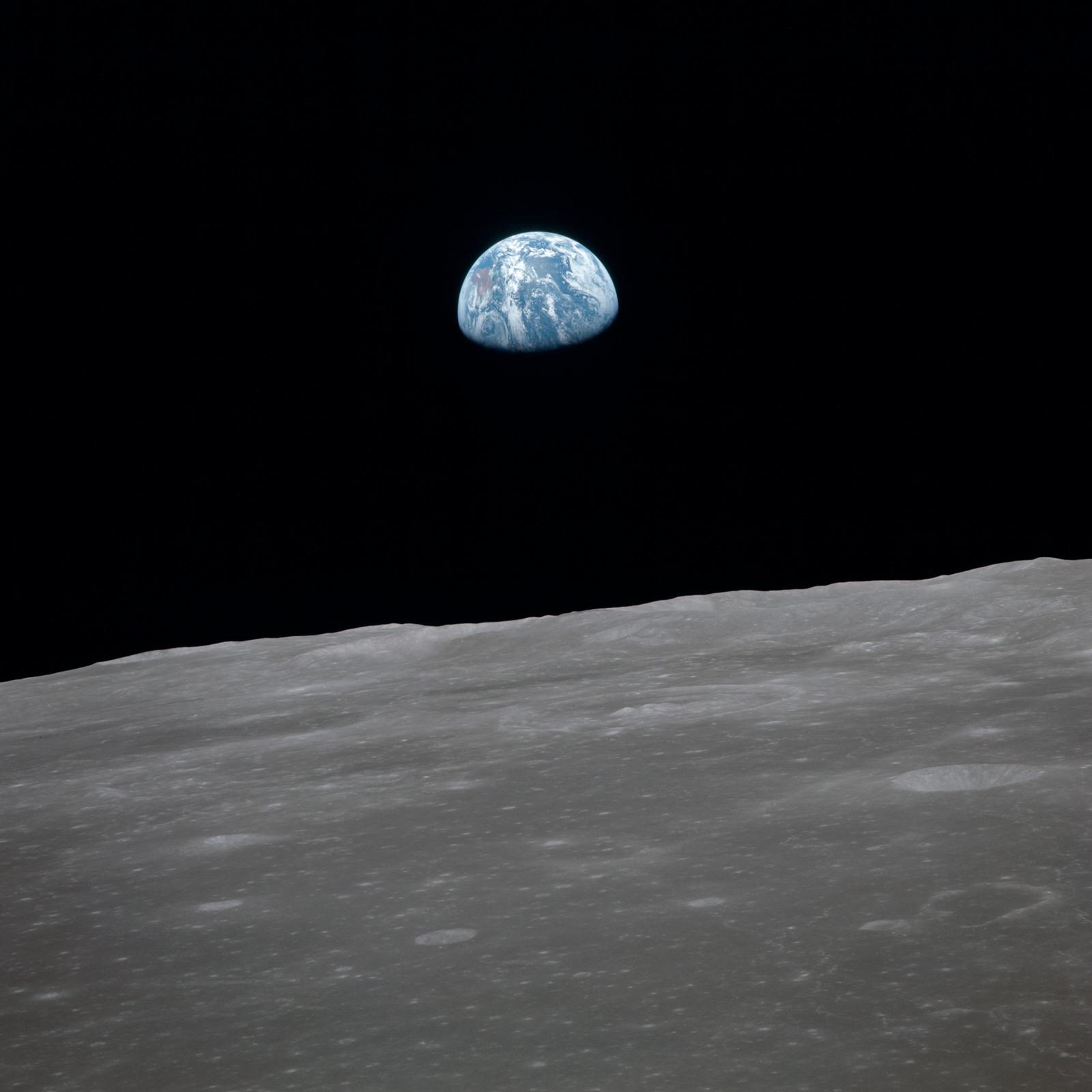 AS11-44-6561 - Apollo 11 - Apollo 11 Mission image - View of moon limb, with Earth on the horizon, Mare Smythii Region