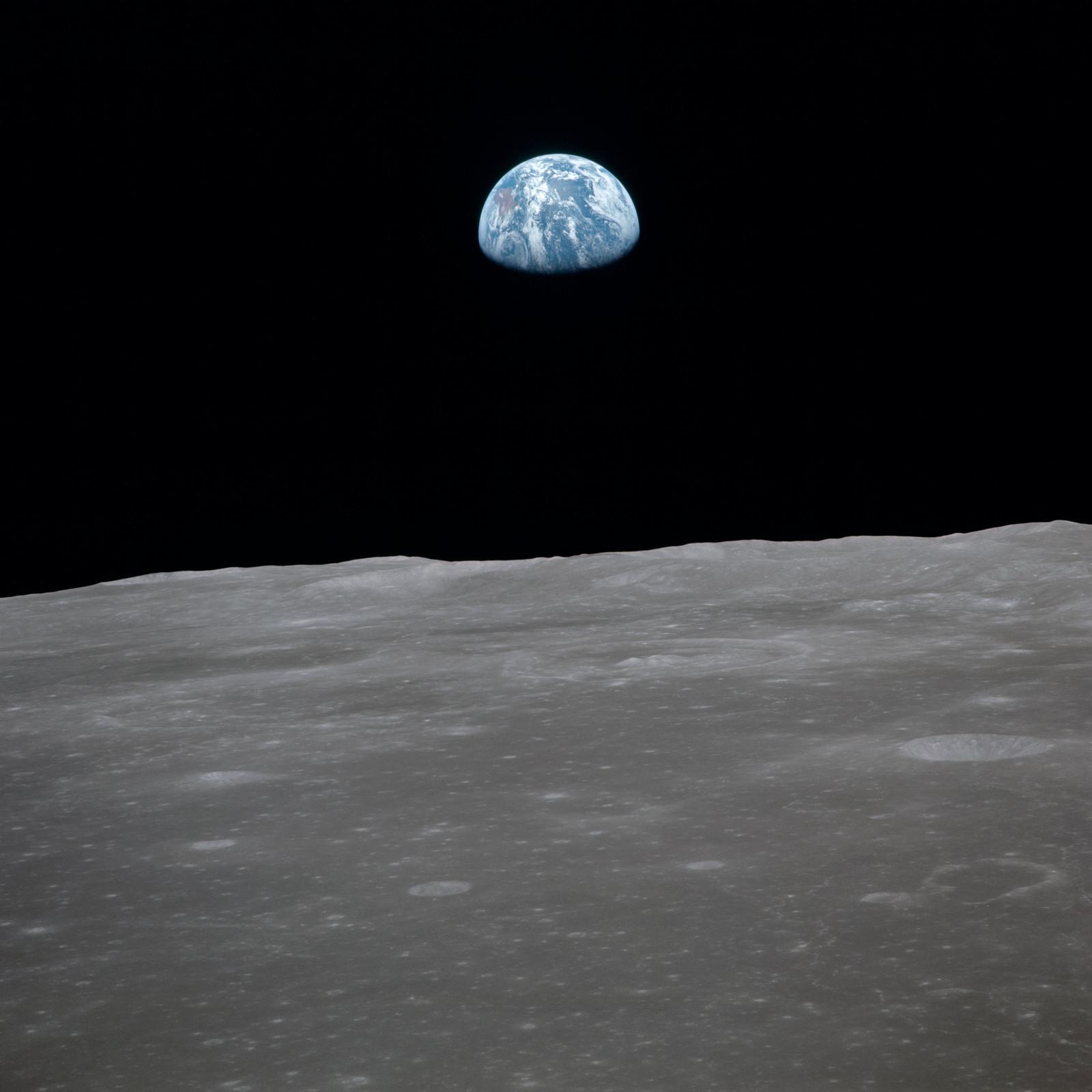 AS11-44-6562 - Apollo 11 - Apollo 11 Mission image - View of moon limb, with Earth on the horizon, Mare Smythii Region