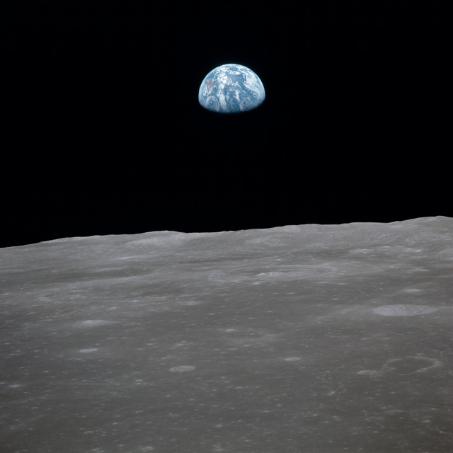AS11-44-6562 - Apollo 11 - Apollo 11 Mission image - View of moon limb, with Earth on the horizon, Mare Smythii Region