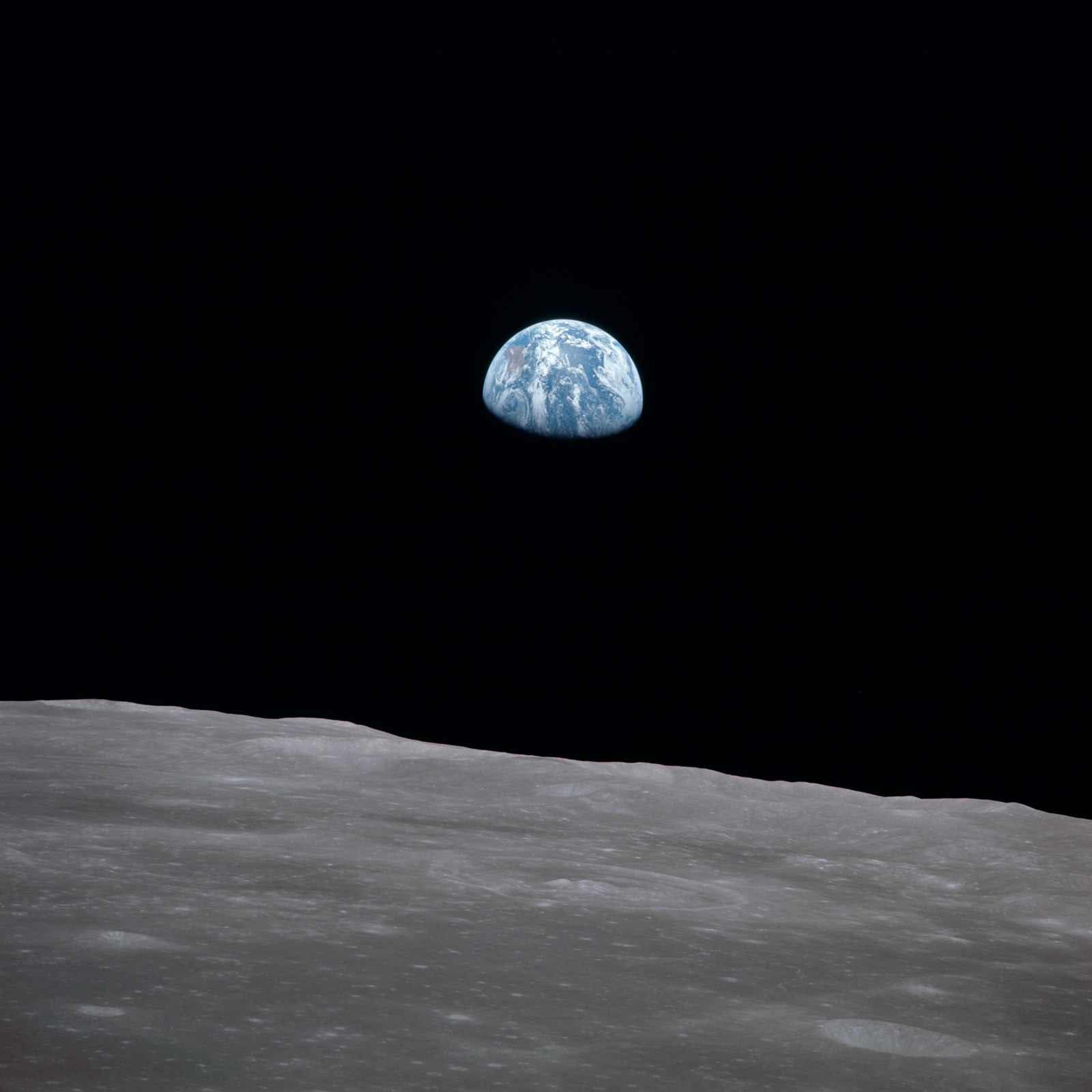 AS11-44-6564 - Apollo 11 - Apollo 11 Mission image - View of moon limb, with Earth on the horizon, Mare Smythii Region