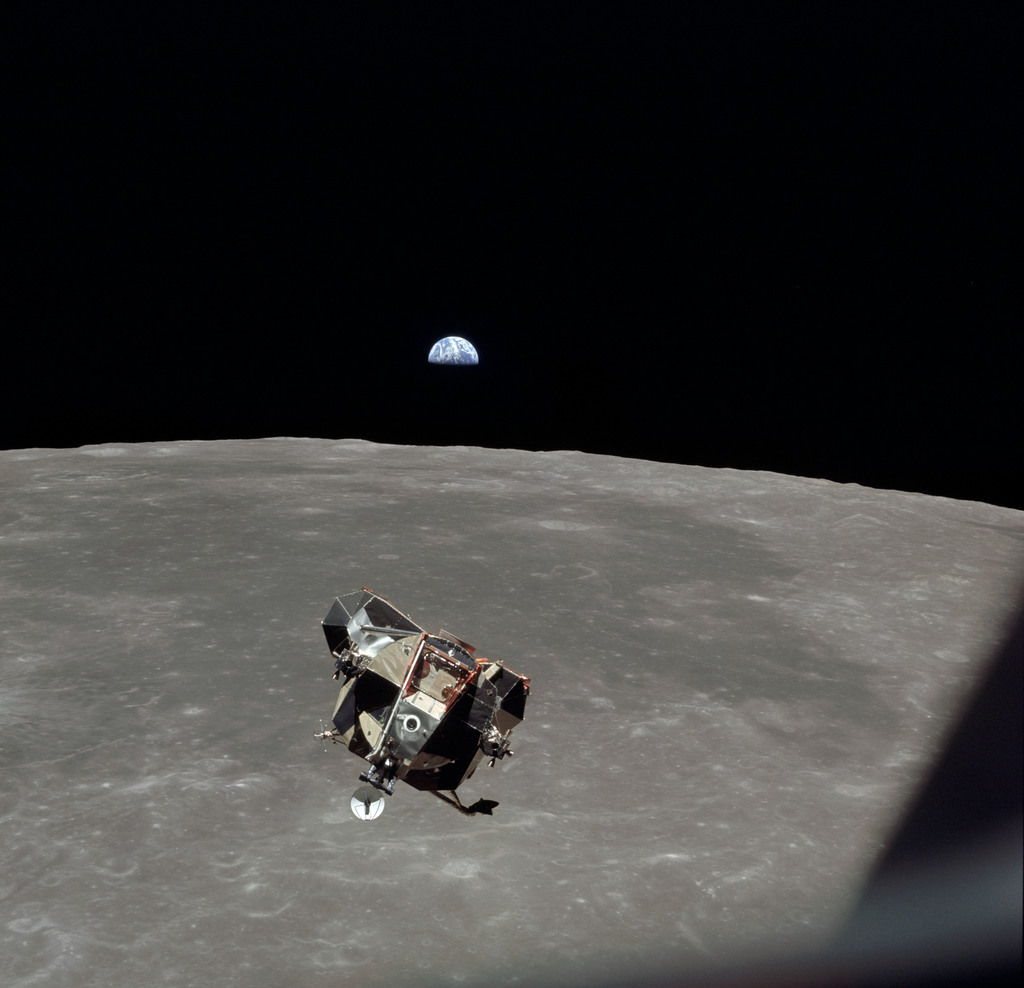 AS11-44-6642 - Apollo 11 - Apollo 11 Mission image - View of Moon limb and Lunar Module during ascent, Mare Smythii, Earth on horizon