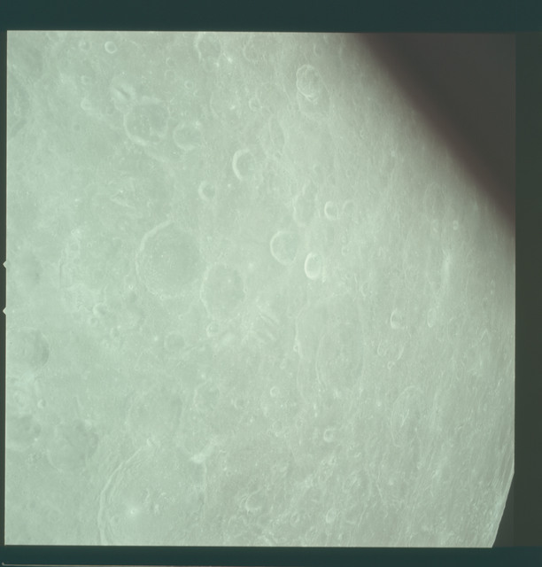 AS11-44-6644 - Apollo 11 - Apollo 11 Mission image - View of Moon limb, Craters 206 and 205, Mare Marginis and TO 53, 55 and 57