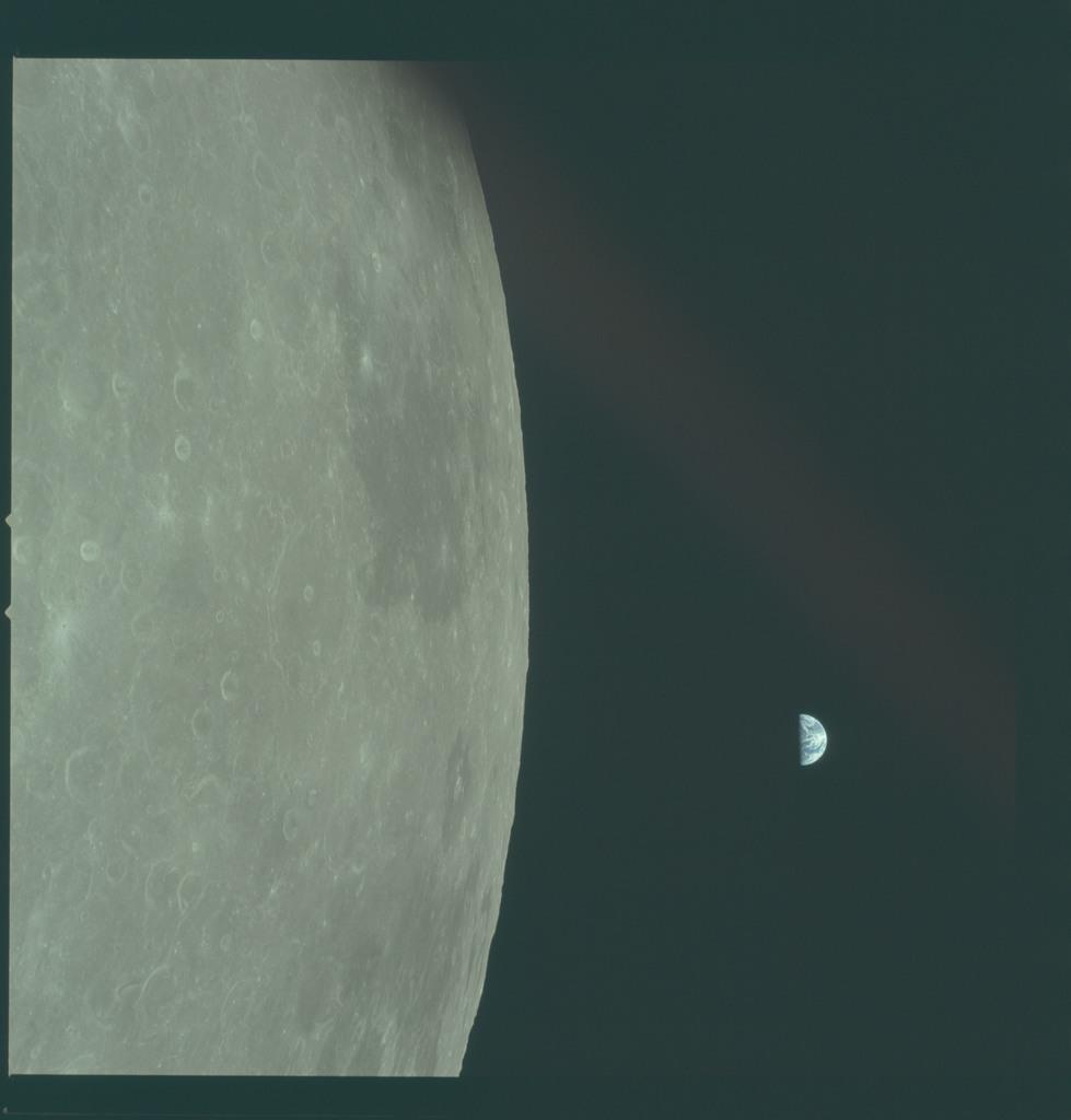 AS11-44-6653 - Apollo 11 - Apollo 11 Mission image - View of Moon limb, Mare Smythii, TO 57 and 61, Earth over horizon