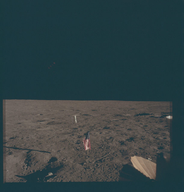 AS12-46-6861 - Apollo 12 - Apollo 12 Mission image  - View of the Solar Wind Panel, flag and deployed erectable S-band antenna