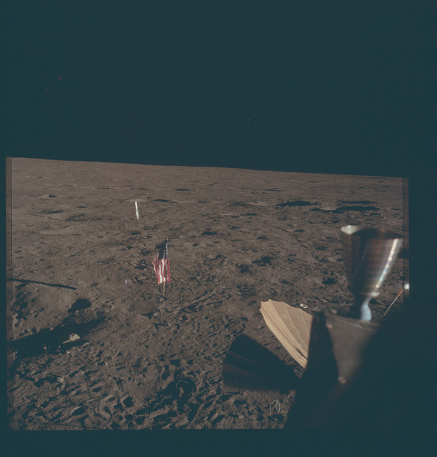 AS12-46-6865 - Apollo 12 - Apollo 12 Mission image  - View of the Solar Wind Panel, flag and deployed erectable S-band antenna