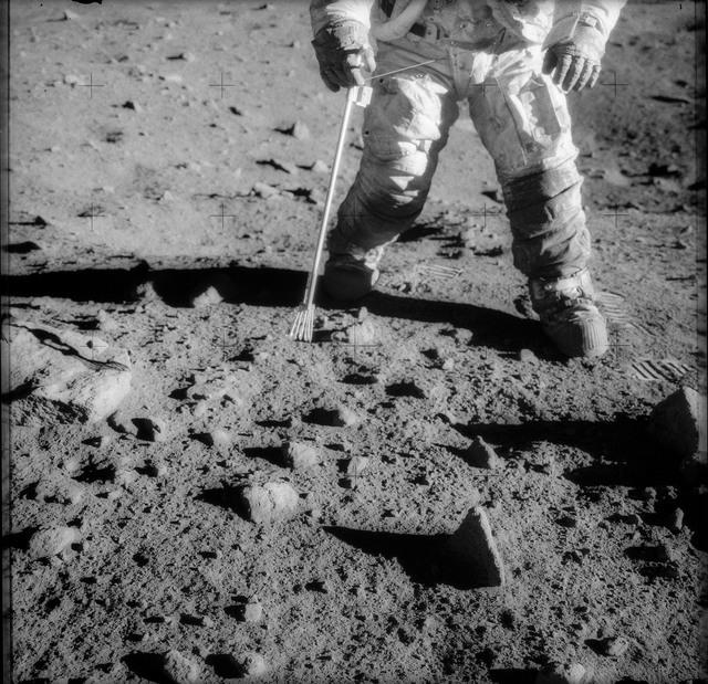 AS12-48-7149 - Apollo 12 - Apollo 12 Mission image  - Charles Conrad Jr., Apollo 12 commander  using tongs