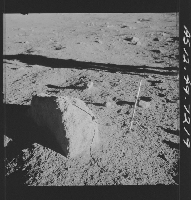AS12-49-7219 - Apollo 12 - Apollo 12 Mission image  - View of a core sampler and a large rock
