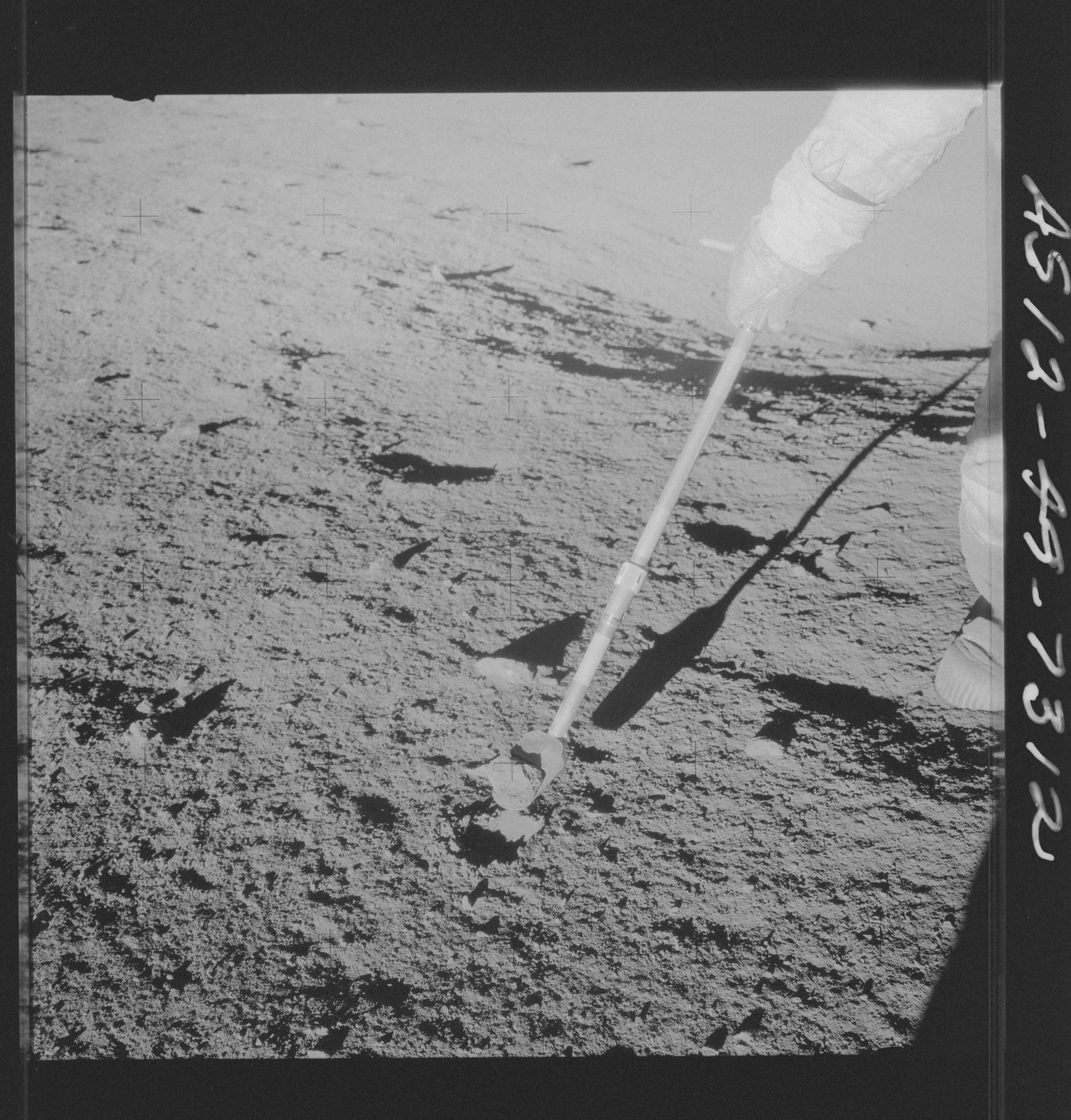 AS12-49-7312 - Apollo 12 - Apollo 12 Mission image  - Charles Conrad Jr., commander, is photographed collection rocks