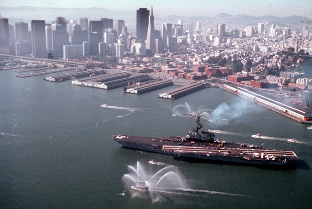 A harbor tug sprays water to welcome the aircraft carrier USS CORAL SEA (CV-43) as other small craft escort the vessel into port