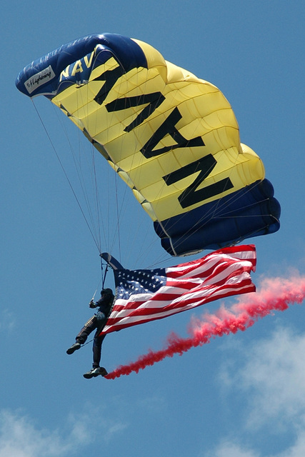 "A member of the US Navy (USN) Parachute Demonstration Team the ""Leap Frogs,"" descends from the sky into Civic Park, displaying the National ENSIGN, during Navy Week Denver and Cinco de Mayo festivities. Navy Week - Denver is one of 20 such events, arranged by the Navy Office of Community Outreach (NAVCO), planned for the year in cities throughout the US"