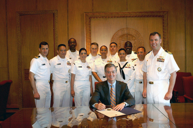 Governor of Colorado, The Honorable Bill Owens (R-CO) signs a proclamation, flanked by US Navy (USN) Sailor, marking the beginning of Navy Week 2006. Navy Week Denver is one of 20 such weeks, planned this year in cities throughout the country arranged by the Navy Office of Community Outreach