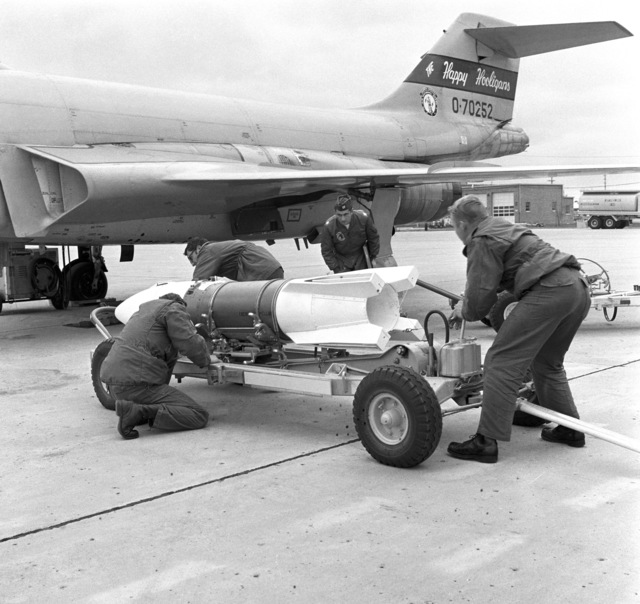 """U.S. Air Force Weapons Handlers assigned to the 119th Fighter Wing""""Happy Hooligans"""", North Dakota Air National Guard, prepare to upload a training weapon onto a F-101B Voodoo aircraft, under the watchful eye of a competition judge, during the""""William Tell""""Weapons Competition at Tyndall, Air Force Base, Florida. (A3604) (U.S. Air Force PHOTO) (Released)"""
