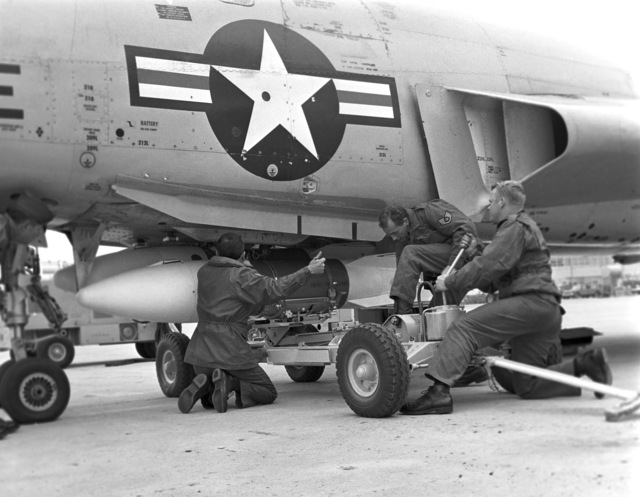 """U.S. Air Force Weapons Handlers TECH. SGT. William Gilge and TECH. SGT. Kenneth Smallerz, both assigned to the 119th Fighter Wing""""Happy Hooligans"""", North Dakota Air National Guard, upload training weapons onto a F-101B Voodoo aircraft, under the watchful eye of a competition judge, during the""""William Tell""""Weapons Competition at Tyndall, Air Force Base, Florida. (A3604) (U.S. Air Force PHOTO) (Released)"""