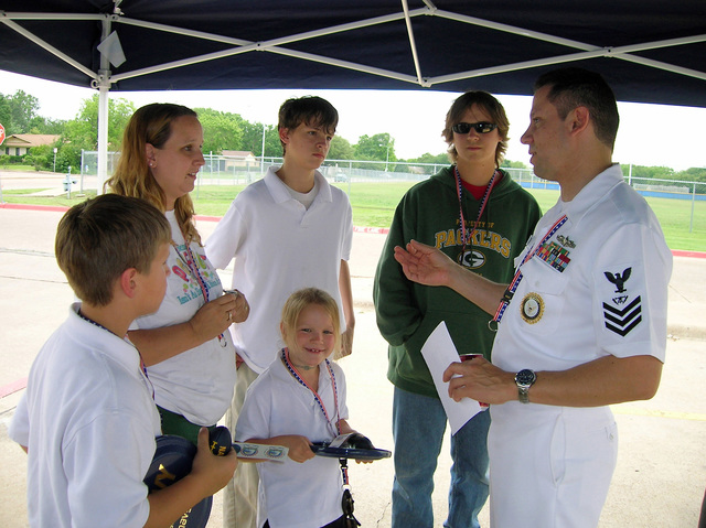 US Navy (USN) Fire Controlman First Class (FC1) Gabriel DeLaPaz, Jr. (right), The CHIEF MASTER Recruiter assigned to Navy Recruiting Station Garland, Texas (TX), explains career options to a South Garland High School student and his family members, during the Navy Week Dallas program, sponsored by the Navy Office of Community Outreach. Twenty other such weeks are planned this year in cities throughout the Country