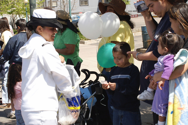 "US Navy (USN) Machinist's Mate Second Class (MM2) Mirna Cabral, Navy Recruiting District (NRD) Denver, hands out USN promotional items, while participating in the ""Cinco de Mayo Celebrate Culture"" Parade, during Navy Week Denver. Navy Week - Denver is one of 20 such events, arranged by the Navy Office of Community Outreach (NAVCO), planned for the year in cities throughout the US"