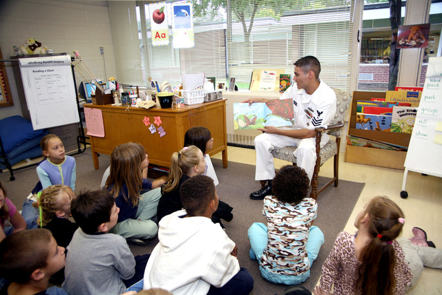 U.S. Navy Yeoman 1ST Class Jose Wrangal reads a book to students at Arnold Elementary School during Navy Week at Lincoln, Nebraska, on Sept. 21, 2006. wenty-six such weeks are planned in cities throughout the U.S. arranged by the Navy Office of Community Outreach, a unit tasked with enhancing the Navy's brand image in areas with limited exposure to the Navy. (U.S. Navy photo by CHIEF Mass Communication SPECIALIST Gary Ward) (Released)