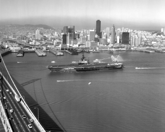 The aircraft carrier USS CORAL SEA (CV 43) approaches the San Francisco-Oakland Bay Bridge on its way to Naval Air Station, Alameda