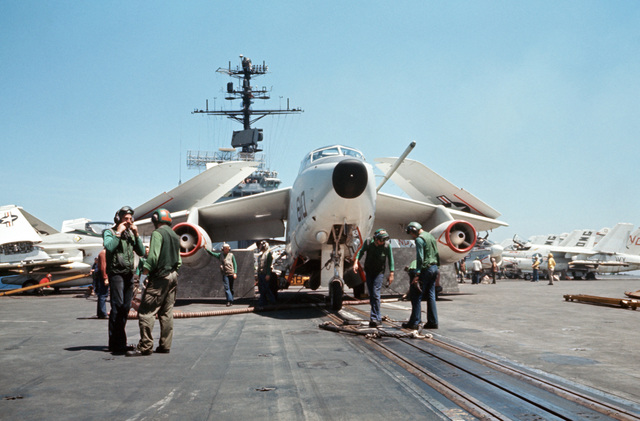 Flight deck crewmen attach an A-3D Skywarrior aircraft to a catapult during flight operations aboard the attack aircraft carrier USS AMERICA (CVA 66)
