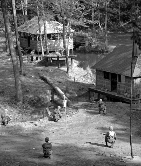 A fire team of marine officer candidates from The Basic School are slowly approaching a hut near the edge of a mockup Southeast Asian village