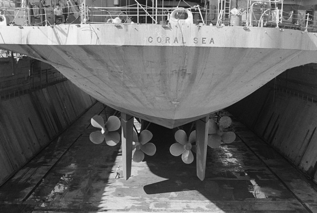 The stern of the aircraft carrier USS CORAL SEA (CV 43), just before flooding of the dry dock. The propellers and rudders are visible