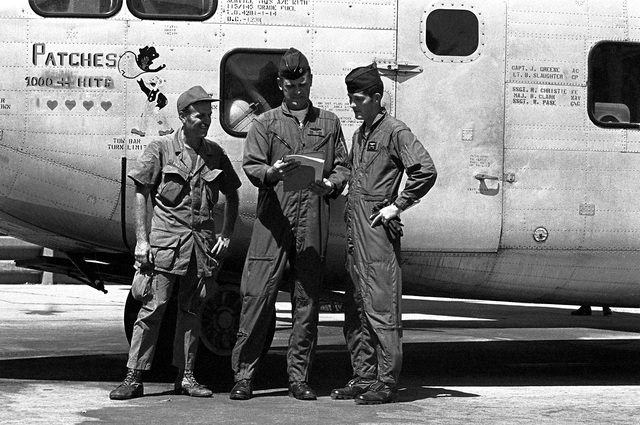 """315th Tactical Airlift Wing members, SSGT W. Pase, MAJ B. Clark and SSGT R. Christie, left to right, pose beside a UC-123K Provider aircraft. The aircraft, being inactivated, is named """"Patches"""" for the more than 1,000 hit-hole patches that it received during the Vietnam conflict"""
