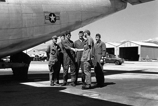 """COL Ray C. Staley, commander, 315th Tactical Airlift Wing, greets a UC-123K Provider aircraft crew. The crew members, left to right, are SSGT W. Pase, SSGT R. Christie, CPT J. Greene, MAJ B. Clark and LT B. Slaughter. The aircraft, being inactivated, is named """"Patches"""" for the more than 1,000 hit-hole patches that it received during the Vietnam conflict"""