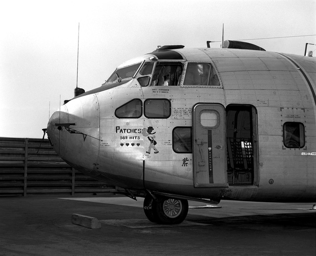 """Left side view of a parked UC-123K Provider aircraft from the 315th Tactical Airlift Wing. The aircraft, being inactivated, is named """"Patches"""" for the more than 1,000 hit-hole patches that it received during the Vietnam conflict. The images painted on the aircraft are Snuffy Smith wearing a bullet-riddled hat and four Purple hearts, one for each aircrew member wounded in flight"""