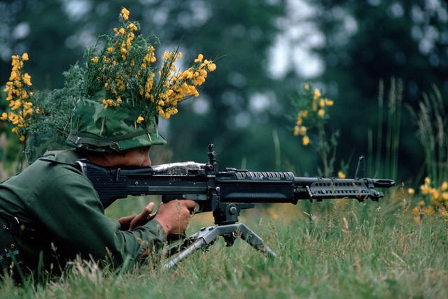 An camouflaged infantryman armed with an M60 machine gun