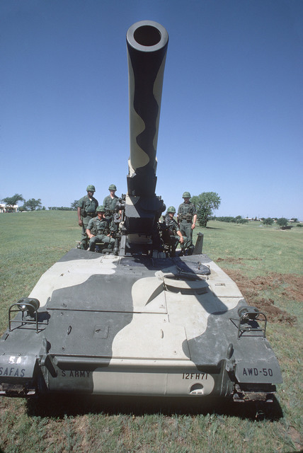 Crewmen of an M110 203 mm self-propelled howitzer man their positions