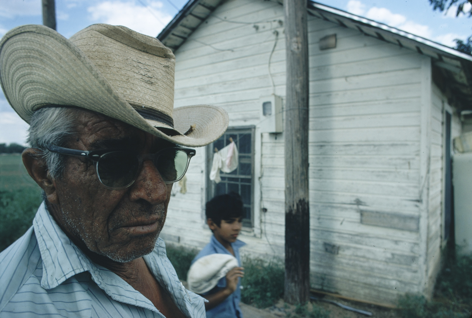 Migrant Worker with His Grandchildren in Front of Two Room Shack Which Houses Three Families (20 People), this Man and His Family Follow the Crops North From Texas Each Year, His Present Job is Weeding Sugar Beets at $2.00 an Hour
