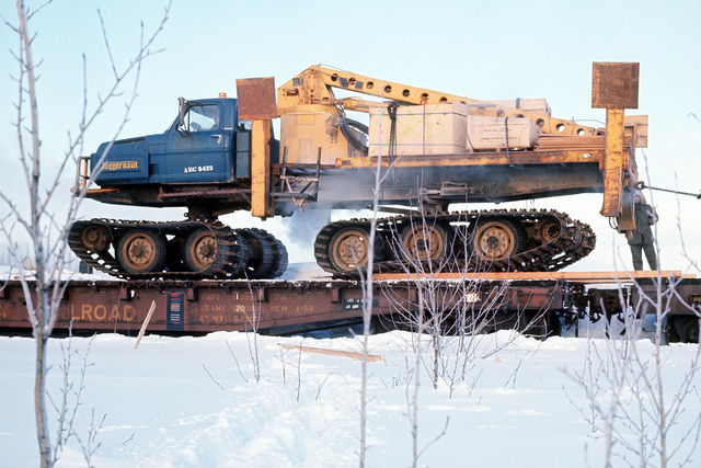 Left side view of a CU-Juggernaut crane on a flatbed railroad car. The Juggernaut will be used to transport men and building equipment on the construction site