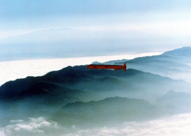 A U.S. Navy Tomahawk cruise missile flies over mountainous terrain after being launched from a submerged submarine