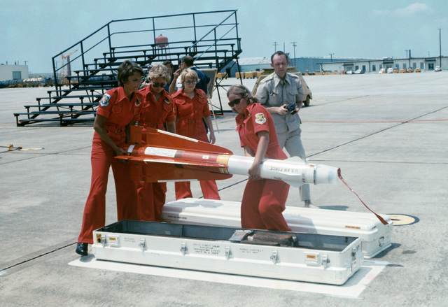 """A U.S. Air Force all female weapons load team assigned to the 119th Fighter Wing""""Happy Hooligans"""", North Dakota Air National Guard, handle an inert AIM-4C Falcon air-to-air missile during a William Tell""""Weapons Competition at Tyndall, Air Force Base, Fla. Pictured from left to right, Doreen Thomas, Patricia McMerty, Jacqueline Sanders, Ellen Rising (ranks at the time are unknown). (A3604) (U.S. Air Force PHOTO) (Released)"""