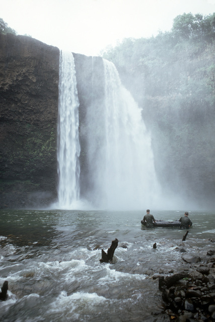 Two US Army soldiers maneuver a rubber boat at the base of a waterfall during a field training exercise