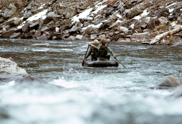 Army personnel use a rubber raft to cross a whitewater river during a training exercise