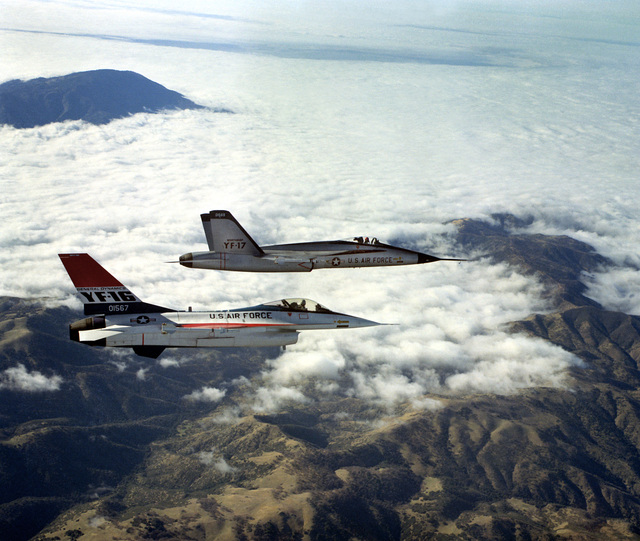 AN air-to-air right side view of a YF-16 aircraft and a YF-17 aircraft, side-by-side, armed with AIM-9 Sidewinder missiles