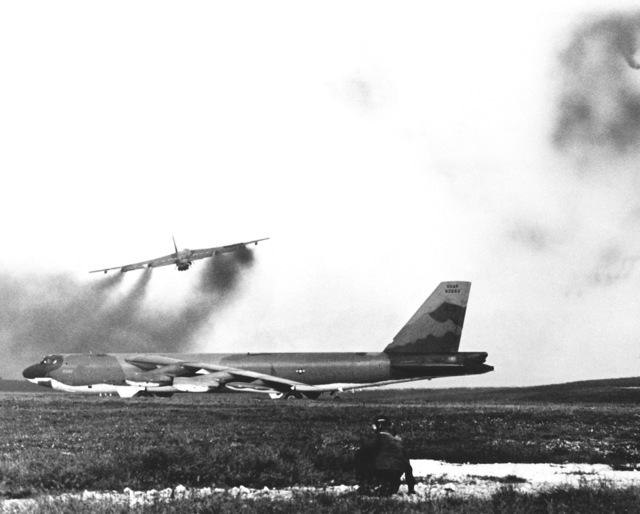 A B-52D Stratofortress aircraft, from Strategic Air Command, leave a smoke trail behind as they take off, one after another, for bombing missions over North Vietnam during Operation LINEBACKER