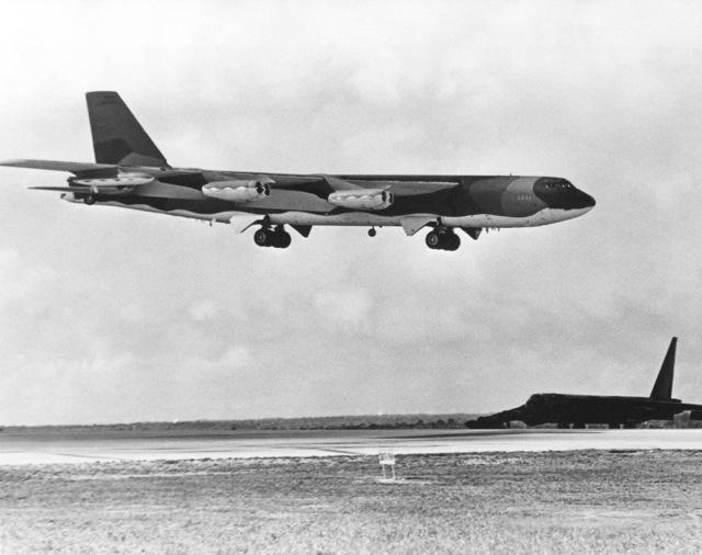 A B-52D Stratofortress aircraft waits beside the runway as a B-52G approaches for landing after completing a bombing mission over North Vietnam during Operation LINEBACKER. The aircraft are from the Strategic Air Command