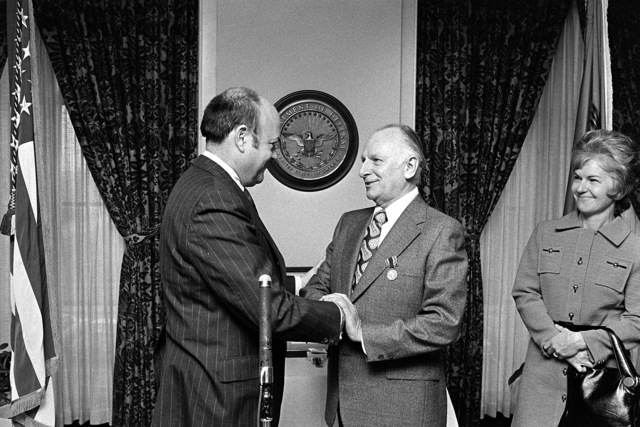 Secretary of Defense Melvin R. Laird, left, congratulates Robert C. Moot, assistant secretary of defense (comptroller), after presenting him with the Department of Defense Distinguished Public Service Medal during a ceremony at the Pentagon. Moot has served in his position since August 1, 1968. Standing on the right is his wife