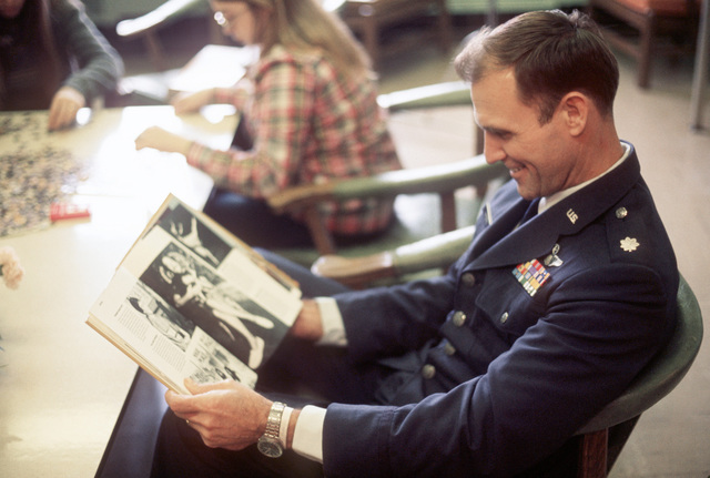 A returnee from a Vietnamese prisoner of war camp catches up on events upon his arrival at Travis Air Force Base