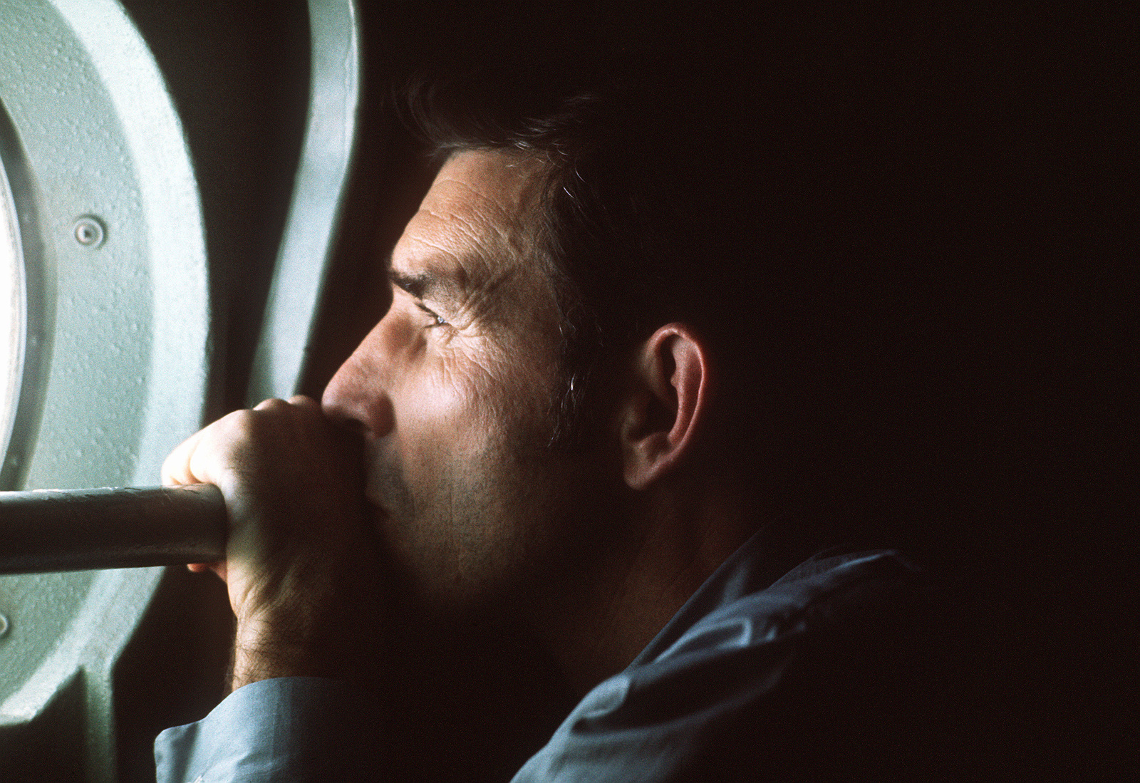 A returnee looks through the window aboard a C-141 Starlifter aircraft. The aircraft is being used to evacuate prisoners of war to Clark Air Base, Republic of the Philippines
