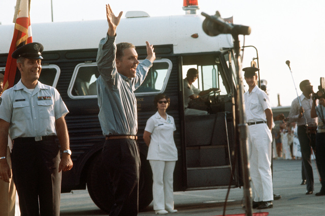 A returnee shows his happiness as he prepares to board a bus at Clark Air Base shortly after being released from a prisoner of war camp in Vietnam