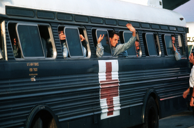 A returnee waves from a hospital bus at Clark Air Base shortly after being released from a prisoner of war camp in Vietnam
