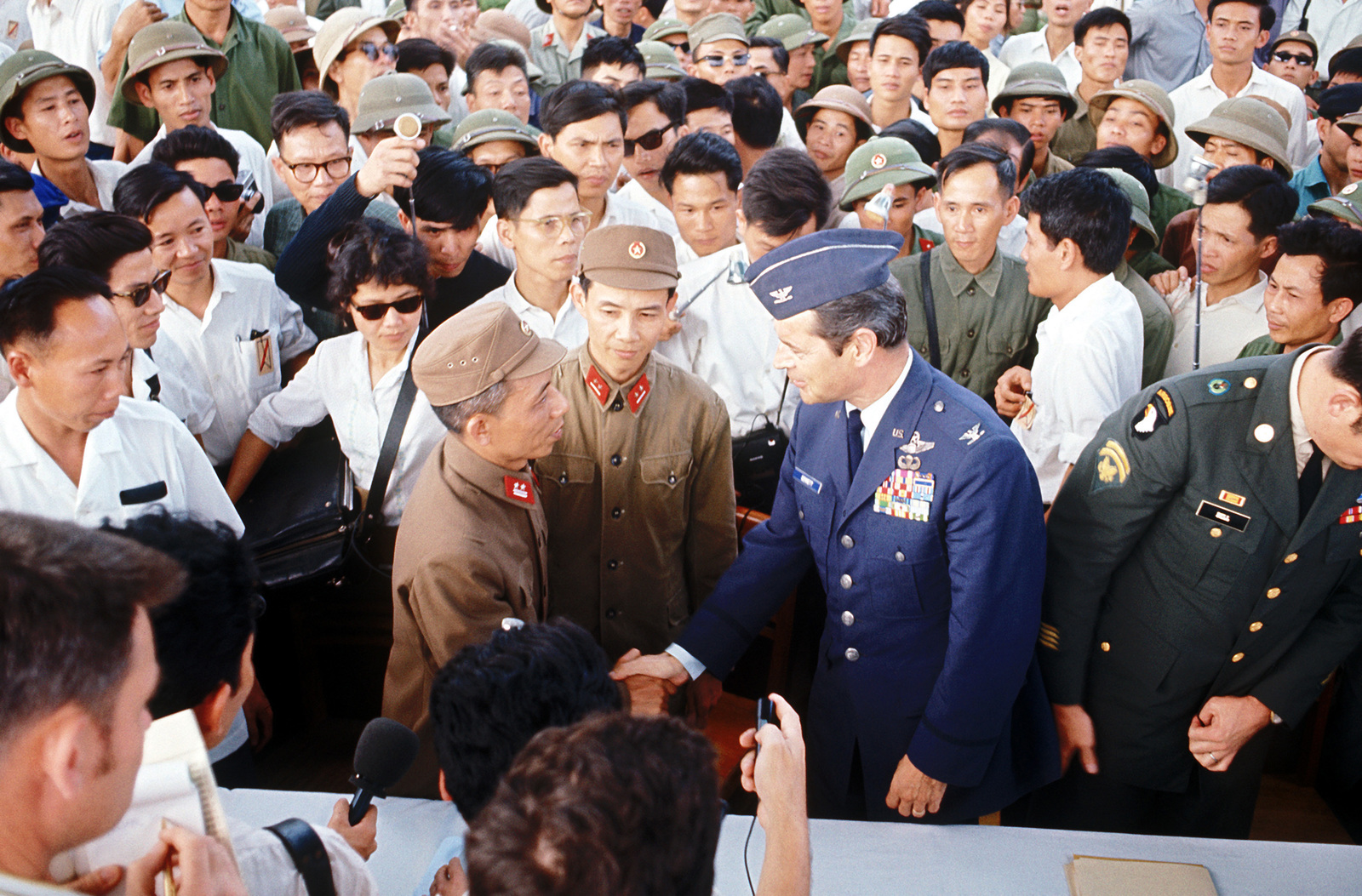 An unidentified U.S. Air Force Colonel, part of the prisoner of war returnee delegation, shakes hands with Vietnam officers as a crowd of news media and spectators look on