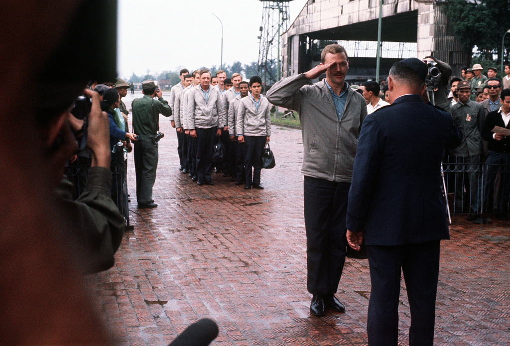 CAPT. John Parsels is greeted by the Gia Lam Airport returnee delegation upon his release from a prisoner of war camp