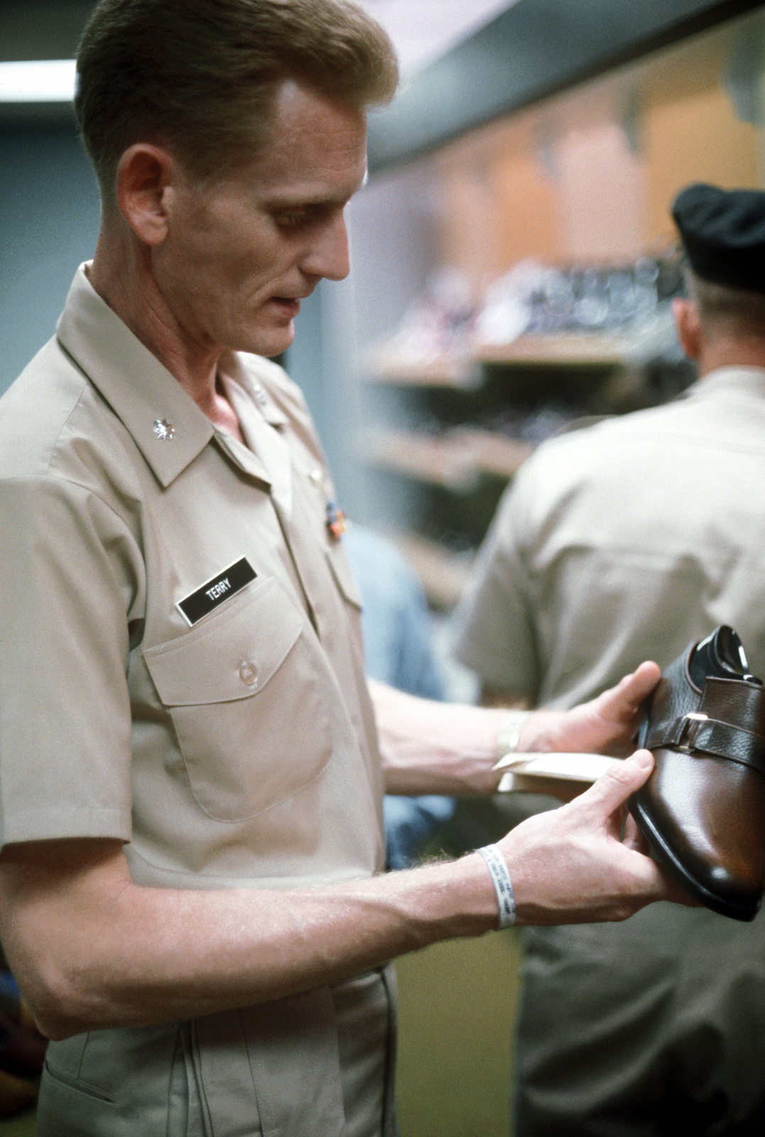 CDR Ross Terry looks at shoes at the base exchange shortly after being released from a prisoner of war camp in Vietnam
