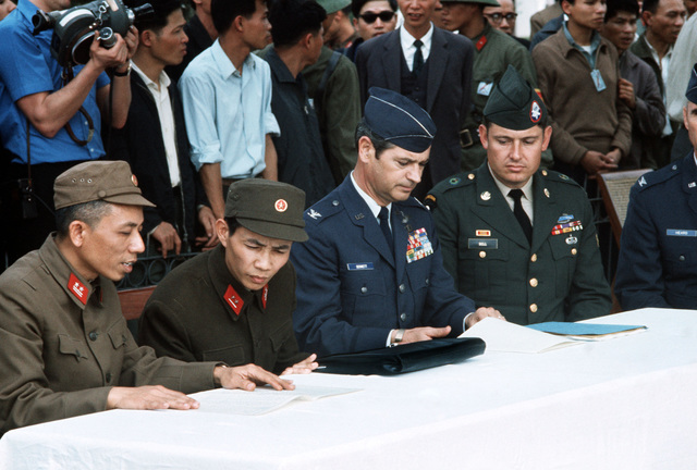 From right to left: COL Heard, SPC 6 Bell and COL J.P. Dennett, part of the Gia Lam Airport returnee delegation, as they discuss release of the American prisoners of war