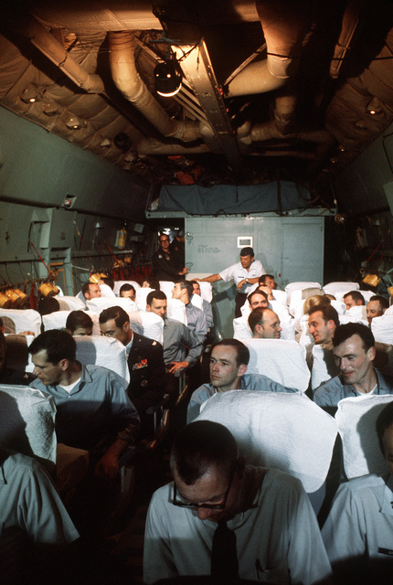 Interior view of a C-141 Starlifter aircraft en route to Clark Air Base, Republic of the Philippines with recently released prisoners of war camp