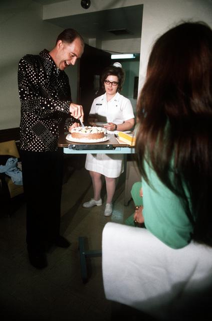 Mr. James Rollins, a recently released prisoner of war, enjoys a cake celebrating his arrival at Travis Air Force Base
